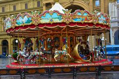 """Florence. On the Piazza della Republica is a carousel with 20 horses and two gilded """"king's carriages."""" The carousel is made of wood and is gaily painted in reds and blues. It also boasts two flowerpots with fresh flowers in them. This is the antique carousel of the Picci family (as is stated in a panel along the top), and it goes around and around every day in November through May,"""