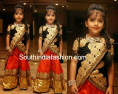 Pretty girl looks adorablein half saree featuring red lehenga with gold shimmer border, black duppatta with gold floral cut work border teamed up with black high neck blouse. Love!! Related PostsKids Designer LehengasKids Half SareeBhargavi Kunam's prettylicious lehengas for kidsKids Traditional Lehengas