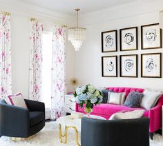 Girly contemporary living room boasts two rows of black and white abstract art in gold and black beveled frames hung above a hot pink velvet couch accented with gray shag pillows and a silver metallic pillow.