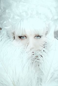 A lady wrapped in white fur very cozy looking