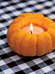 Pumpkin Votive For an autumn table, carve out jack-be-little pumpkins and insert votive candles. This festive decoration can be used for Halloween parties, as well as Thanksgiving feasts.