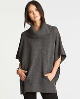 "Merino Wool Blend Poncho - Crafted in a luxe merino wool blend, this versatile style flaunts an effortlessly elegant poncho silhouette that layers beautifully. Ribbed turtleneck. Drop shoulders. Kangaroo pockets. 26"" long."
