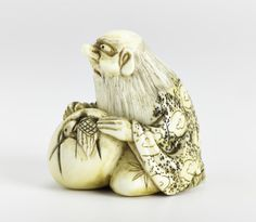 Netsuke of carved ivory, an old man sitting with a bird emerging from an egg, unsigned: Japan, 19th century