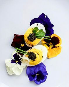 Caviar deviled eggs served on a bed of edible flowers. Visit our site for this festive recipe link in bio.