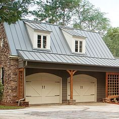 love the standing seam roof, and timber/stone columns offset from the doors, allowing a roof overhanging the garage doors!
