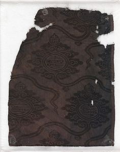 Yuan Dynasty. Damask with cloud palmettes and Chinese characters. Silk satin damask; 27.9 x 21.6 cm. Trade or diplomacy must have played a role in textiles such as this example (originally blue), which, according to records, was found in Egypt. The palmette pattern originated in Central Asia and the eastern Iranian world. Here, it also features a Chinese cloud border and flawlessly rendered versions of the Chinese character for longevity. The Metropolitan Museum of Art.