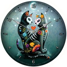 Sitting on a small grassy hillock, two black cats are covered in flowers and the outlines of bones, their white masks giving them the appearance of revelers at Dia de los Muertos. Cool Clocks, Cool Stuff, Night, Cool Watches, Cool Things