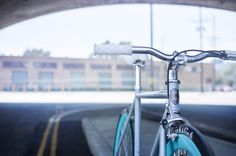 Light grey bike / teal wheels with red hubs.   #purefix #fixie #losangeles