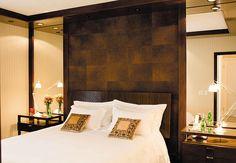 A parede atrás da cabeceira de madeira trabalhada é revestida com placas de couro envelhecido. O quarto de casal ganhou amplitude com a utilização dos espelhos nas laterais do painel