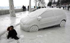 A boy sits in front of an ice covered car in Versoix, near Geneva, Switzerland, on February 5, 2012. Bitterly cold weather sweeping across Europe claimed more victims on Sunday and brought widespread disruption to transport services, with warnings that the chilling temperatures would remain into next week. (Reuters/Denis Balibouse)