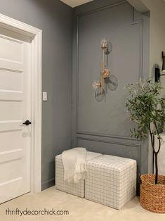 modern accent wall with decorative trim Cozy Basement, Basement Walls, Dark Grey Walls, Thrifty Decor Chick, Brass Sconce, Wall Trim, Square Ottoman, Decorative Trim, Grey Paint