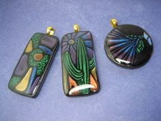 Faux Dichroic Glass Mica Pendants  by Guadalupe Meter  These pendants were created by using Cindy Lietz's tutorial on Faux Dichroic Glass Mica. Mica powders and Lisa Pavelka's Magic Glos (resin) were used in making these polymer clay pendants.