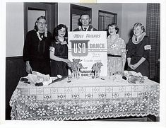 "This photograph, taken during the Korean War, shows two off-duty servicemen and three USO volunteers, donned with leis, at a reception table for an USO-sponsored dance. Men and women stand around a poster advertisement for the event, which promised attendees - exclusively servicemen and USO volunteers, mostly female - that they would ""meet friends"" and have a ""fun, enjoyable evening."" 