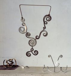 Alexander Calder.   On wall: Necklace, (c. 1943), silver wire; on surface: a) Bracelet, c.1947, gold wire.  b) Cufflinks, c. 1940, silver wire.  c) Tiara, c. 1938, silver wire.   All Calder Foundation, N.Y., photo © Maria Robledo