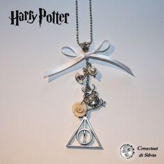 Da appassionata del genere fantasy non poteva mancare fra le mie creazioni un completo con il tema di Harry Potter! Ho realizzato questa collana con dei ciondoli in argento: il simbolo dei doni della morte, un gufo e un cappello da mago. Ho aggiunto una perla swarovski bianca e ho realizzato a mano una rosellina rosa in fimo. La lunghezza della catena a pallini diamantata è di circa 80cm.