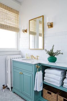 Exquisite bathroom boasts top part of walls painted white and bottom part of walls clad in white subway tiles lined with a Restoration Hardware Antiqued Brass Rivet Medicine Cabinet illuminated by antique brass sconces, Openwork Single Wall Sconces, placed above a turquoise washstand adorned with gold knobs fitted with open shelving.