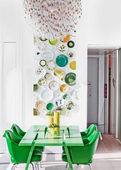 contemporary green and yellow plate wall and green dining table and chairs by Ghislaine Vinas // dining rooms