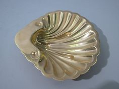 "1 of 2 available shown S. Kirk & Son gilded Sterling Shell Dish Contact:646-863-5416 A lovely American sterling silver figural scallop shell dish that has been gold plated to give the dish its' gilded finish. Made by S. Kirk & Son, Baltimore, Maryland. Circa 1930's. Fully hallmarked, soft gilt finish. Excellent condition, 3 troy ounces, very good weight, measures approximately 5"" x 5"". #GildedSterlingShellDish #FiguralScallopShellDish #FullyHallmarkedSterlingSilver #AntiqueSterlingSilver"