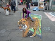 This 3D chalk drawing of girl riding tiger is made by Arndt Nikolaj.
