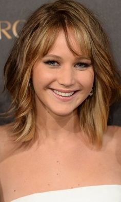 Jennifer Lawrence medium length hairstyle. Cut hair bluntly at the bottom with simple face-framing layers that blend in with long bangs. #hairstyleforroundfaces