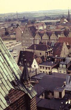 """Rostock, Aufn. Dieter Raskop, 60er Vom Dach der Marienkirche hinunter zum Ernst-Thälmann-Platz (heute Neuer Markt), die südliche Neubebauung des Platzes mit der Post ist schon da, das """"Haus Sonne"""" fehlt noch. Ganz weit im Hintergrund links die alten Gaswerke."""