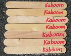 Write Kaboom in red ink on several craft sticks
