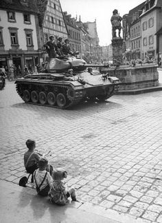Children sitting on curb and watching tank patrol go by | Germany, August 1946 | Walter Sanders