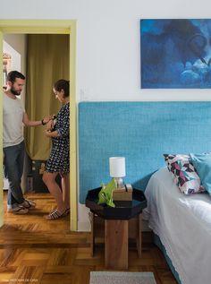 Quarto de casal com cabeceira revestida de tecido azul e almofadas com estampas geométricas.