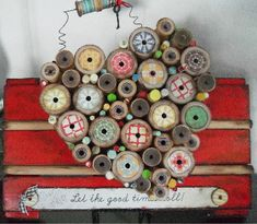 wooden heart with wooden spools and patterned paper over wooden plaque. con carreteles, un corazón folk