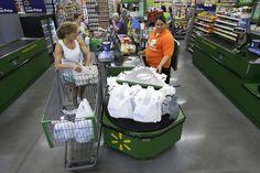 A woman checks out at a Bentonville, Ark., Wal-Mart Neighborhood Market