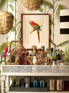 "Bar cart essentials such as a silver champagne bucket were given whimsical new life with the addition of a faux parrot and a pair of tortoise shells. ""Accent what you already have,"" Michelle suggests. ""All you need are a few finishing touches to create a cohesive theme."" Tiki Bar Decor, Bar Cart Decor, Tropical Home Decor, Tropical Interior, West Indies Decor, West Indies Style, Bar Cart Essentials, British Colonial Decor, Home Bar Accessories"