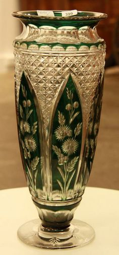 A good Bohemian 19th century tall overlay glass vase, with a deeply cut pattern featuring six dark green spade shaped panels each decorated with floral and leaf motifs