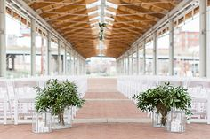 Big bundles of greenery in interesting vases to mark the aisle