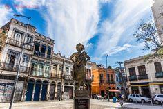 O Largo de São Francisco da Prainha, no Rio de Janeiro, com a estátua de Mercedes Baptista, primeira negra a ser primeira bailarina do Theatro Municipal do Rio de Janeiro. Atrás da estátua, o largo com seus sobrados em estilo português, com paredes coloridas. O céu está azul e limpo, com nuvens brancas.