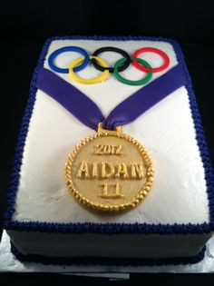 Olympic themed birthday cake made for 11th birthday.  Iced in Buttercream.  Fondant rings, chocolate medal with luster dust.