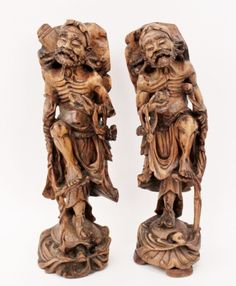 Chinese, 19th century. Pair of two complementary hand carved wood lohans (follower of the eightfold path) or Buddhist arhats depicted with thick curled facial hair, exposed ribs, knee bent and foot resting on staff supported by hand and holding docile creatures in opposite hand standing at full length and riding on stylized ocean waves on the back of a turtle (common imagery from Ming & Qing period depictions of immortal lohans). Unmarked.