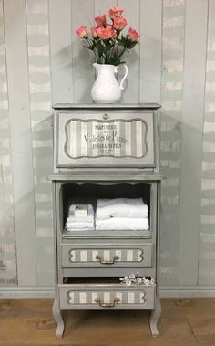 This lovely, sturdy little piece has been refinished with Paris Grey Chalk Paint™️ (Original for the stripes). The hardware has been primed, sprayed gold, and finished with Rub n' Buff Gold Leaf gilding wax.