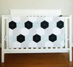 """This modern, hexagon quilt is a gorgeous combination of colors! """"The Cruz"""" is handcrafted with hues of White, Grey, Black & a Light Mint. It has a backing of a light grey with a hint a white speckles."""