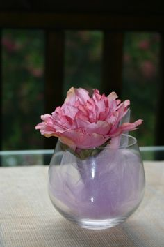 more flower decorations.   Very simply a stemless wine glass with lavender tulle and a silk flower