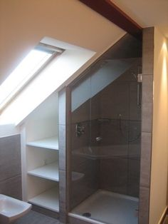 Using up the space under the eaves beside a shower for extra deep shelving.