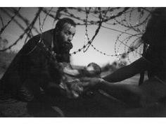 28 août 2015. Frontière serbo-hongroise. Un homme tend un bébé sous les barbelés…
