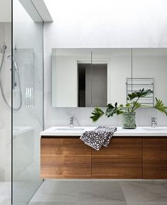 LAYOUT Timber floating vanity, white benchtop and mirrored cabinets above.