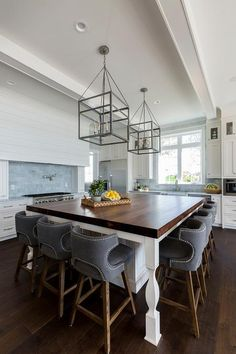 Two glass and iron lanterns hang from a tray ceiling over an oversized white island seating gray low wingback counter stools at a butcher block countertop.