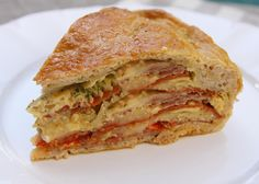 "Pizza Chena: sometimes pronounced ""Pizza Gaina,"" is a southern Italian savory ""pie"" made with a variety of cheese, cold cuts, and eggs baked within a bread crust."