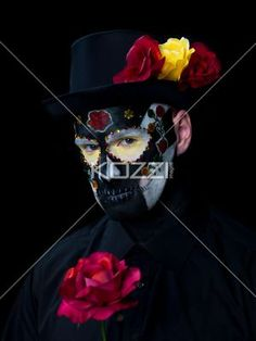 portrait shot of a man with traditional sugar skull make-up. - Portrait image of a scary man wearing traditional sugar skull make-up and black hat with red and yellow roses. Model: Winter Bourne