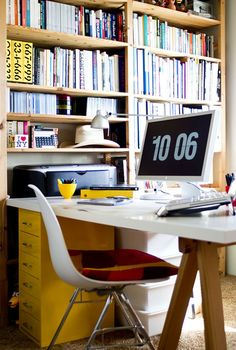 A dream office setup. I love the yellow filing cabinet as a leg for the desk, and all those lovely bookshelves...