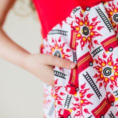 Clang! Clang! Clang! It's a five-alarm dress! Red fire engines and black rescue ladders head off to fight explosive bursts of fire. Little heroines who rush to save the day will love this bright, twirly, 100% cotton dress. Future fire fighters can store treasures in the hidden pockets while out on missions.   Sizes 2T, 3T, 4T, 5, 6, 8, 10, 12.