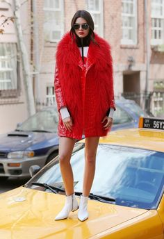 "Kendall Jenner wearing a red fur coat while standing on a New York taxi during her photo shoot with Vogue on April 26, 2015. The brunette reality star is shaking off all the haters and has been vocal about supporting her father, writing ""I love you,"" and ""so very proud of you, my hero"" to Twitter on April 25, 2015."
