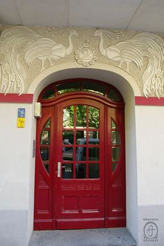 Red Berlin door topped with 2 white peacocks.