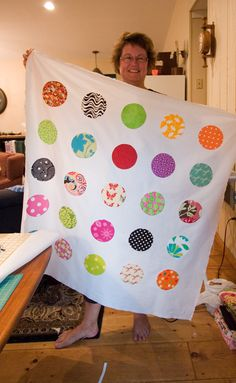 circles -- cut squares of fabric and matching squares of iron-on interfacing. Then on back of fabric trace template (she used a CD).  Place fabric and interfacing (glue side) right sides together.  Stitch on drawn line.  Cut slit in interfacing/invert/finger press (no iron).  Place in desired places on backing fabric.  Iron on to adhere. Then stitch/quilt as desired.